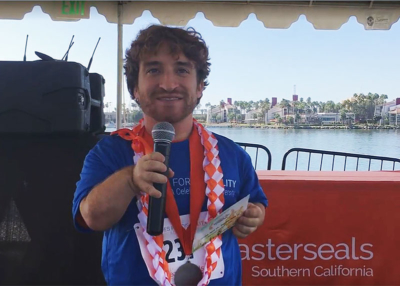 Nic Novicki announcing the dates for the 2018 Disability Film Challenge in front of water