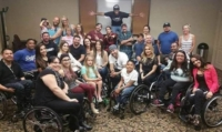 Group photo of the cast of Minority Effect. Most of the cast use wheelchairs and are center in the photo with the rest of the cast standing behind them.
