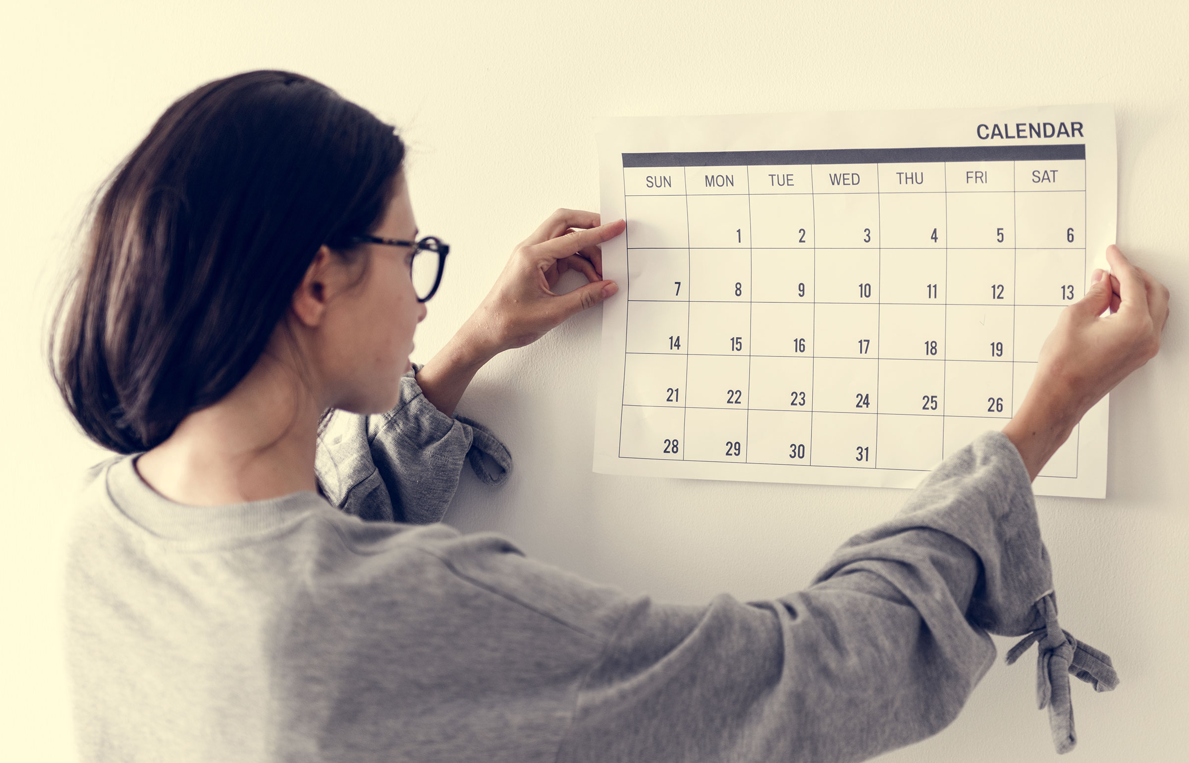Woman wearing eye glasses hangs up a calendar on her wall