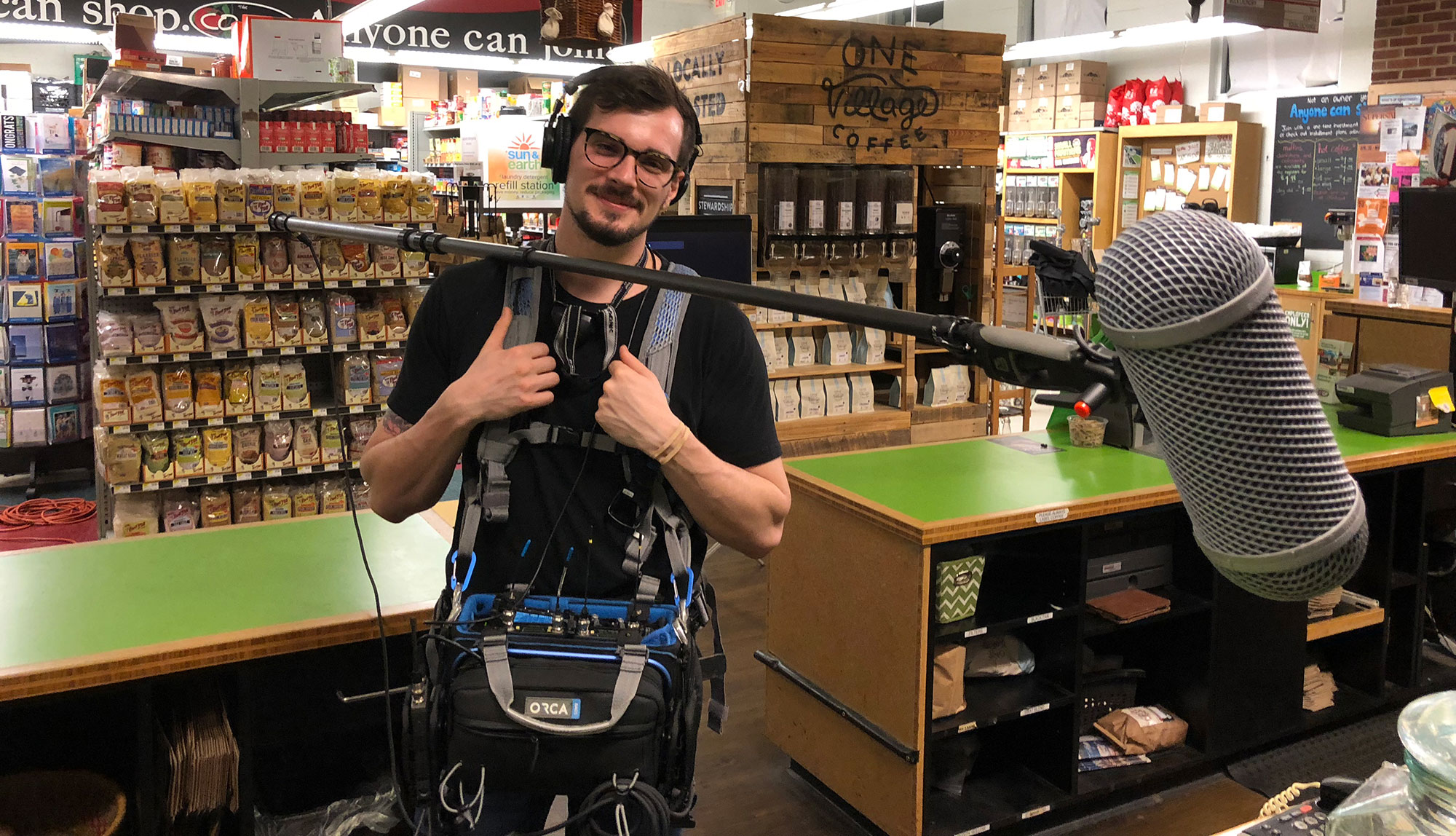 Man wearing sound equipment and a boom mic stands in a store