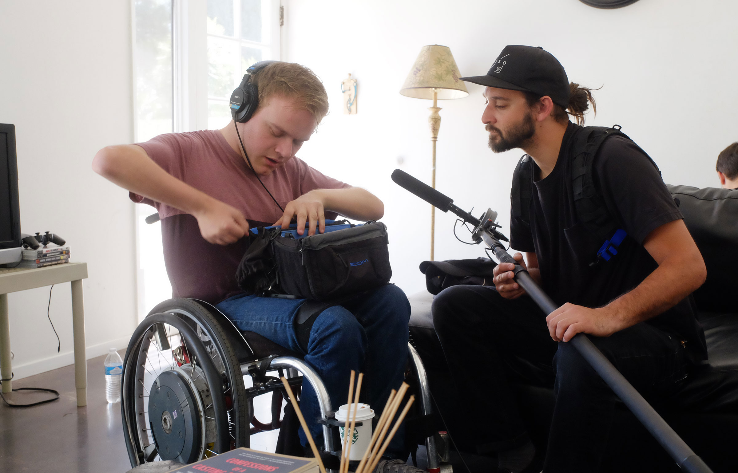 A sound man in a wheelchair talks with a boom mic operator