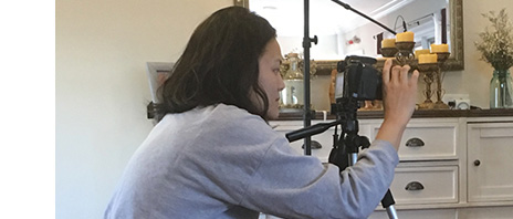Camerawoman filming a scene in a home