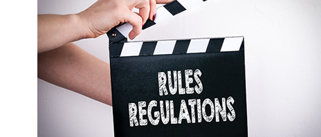 "Film clapperboard with ""Rules Regulations"" written in chalk on it"