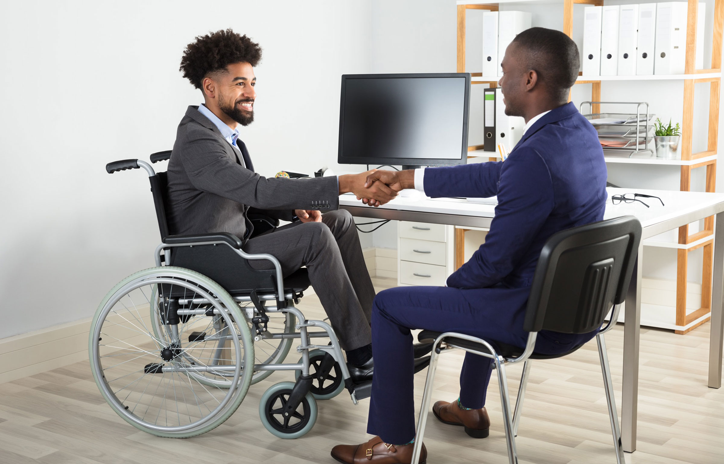 A businessman in a wheelchair shakes hands with a man sitting in a chair