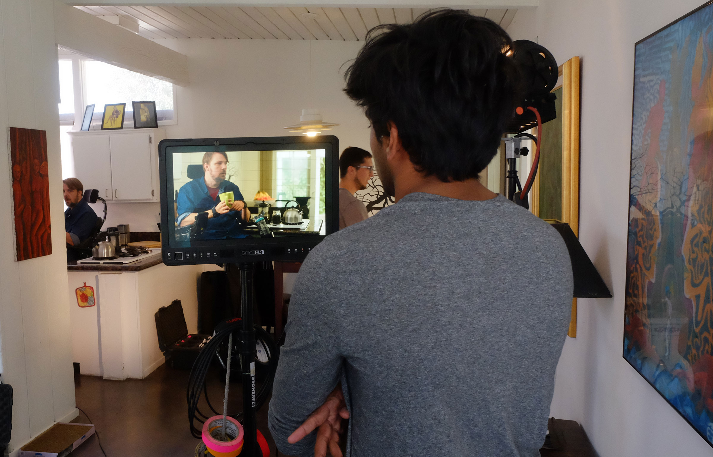 Cameraman watches a film scene on a monitor with the actors in the background